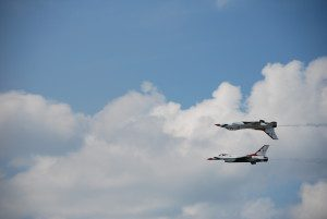 Two jets flying in formation one upside down over the other